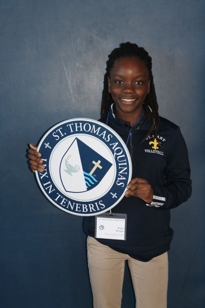8th grade student holding STA seal.