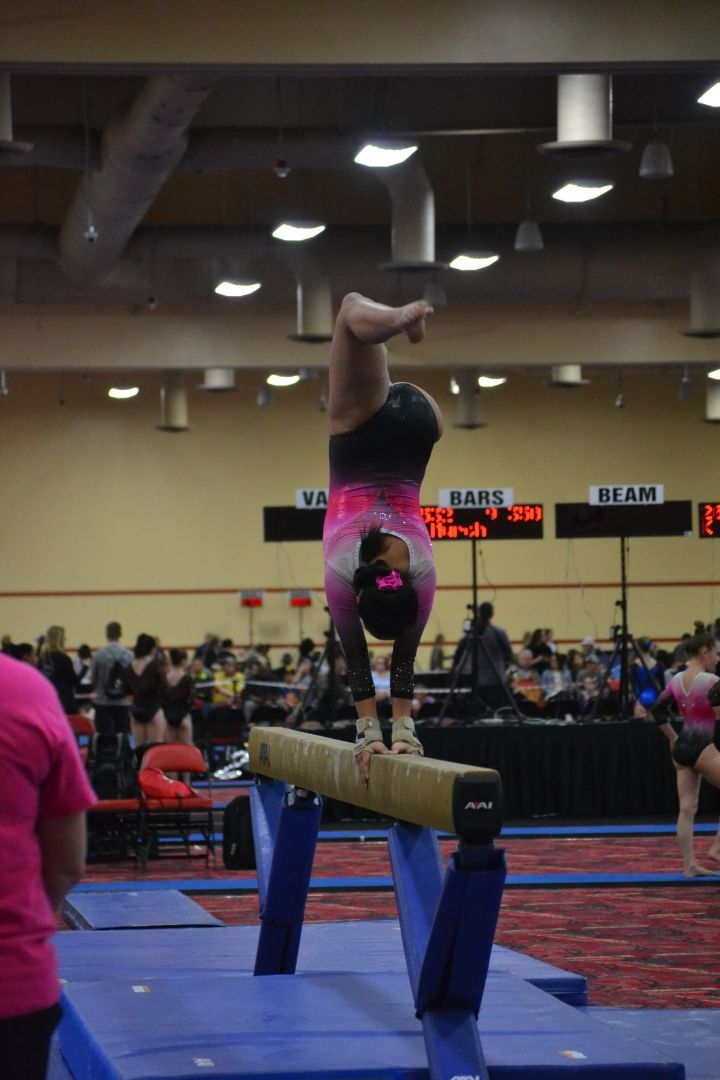 Girl on balance beam.