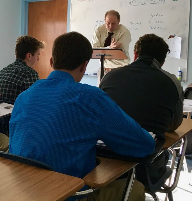 Latin teacher instructs students in classroom.