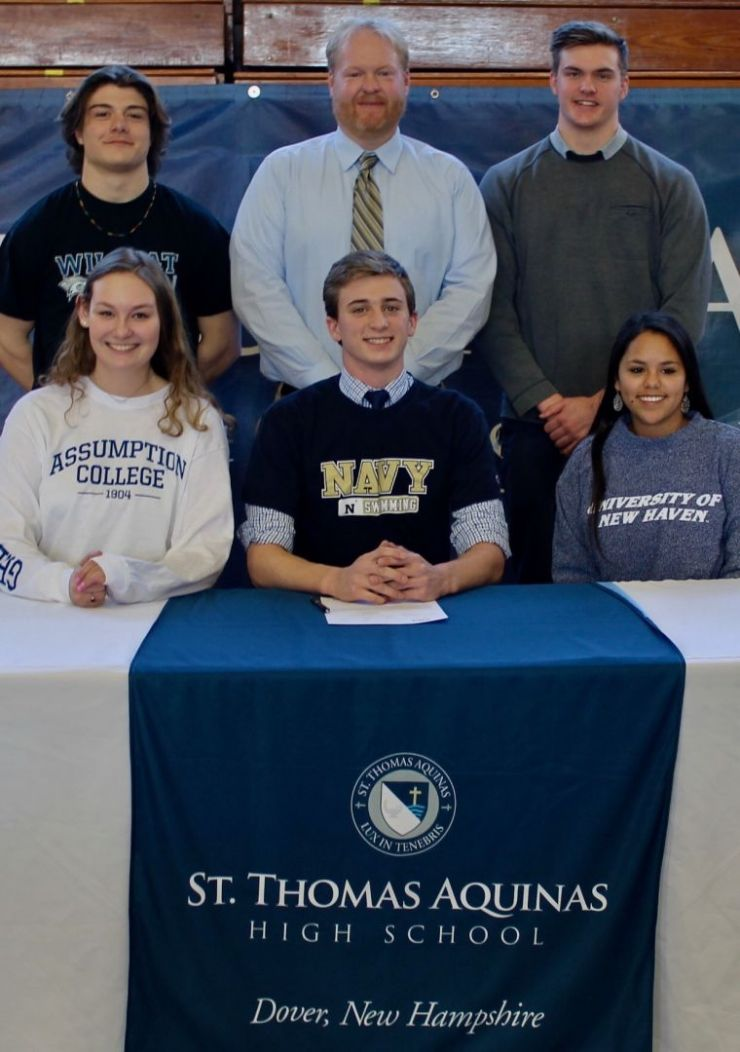 Students pose with their coach on day of signing.