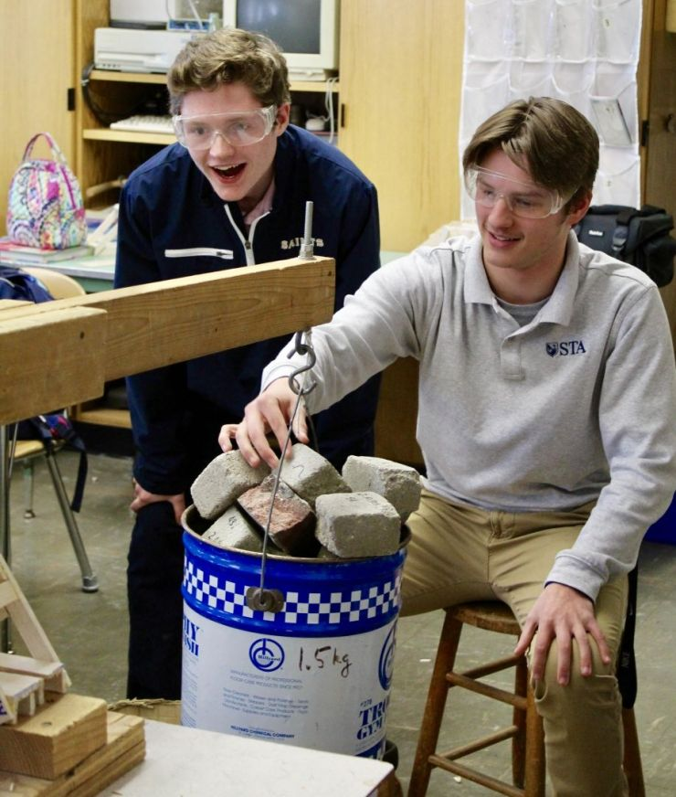 Two male students adding weight in physics class