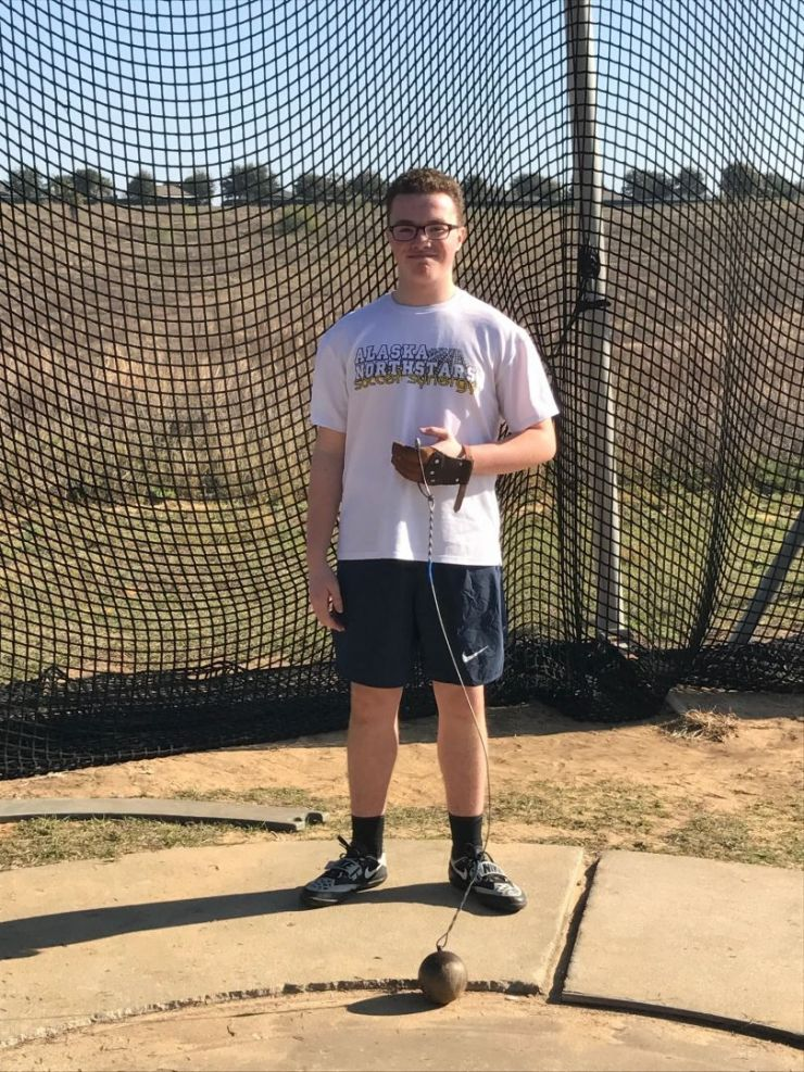 Boy standing with shot put at track and field competition