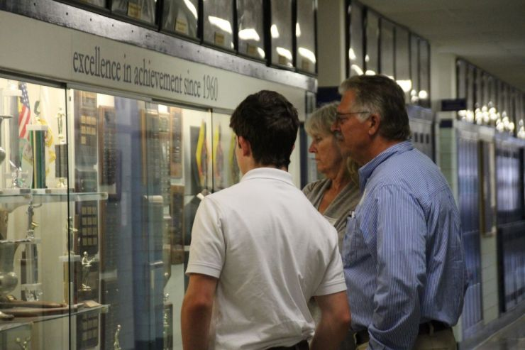 A family looks at the STA trophy case.