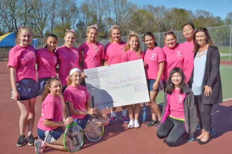 Girls tennis team presents check to non-profit organization